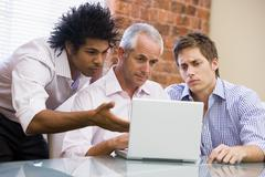 Three businessmen sitting in office with laptop - stock photo