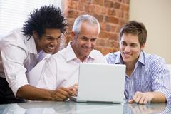 Three businessmen sitting in office with laptop smiling - stock photo