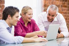 Three businesspeople in office with laptop pointing and laughing - stock photo