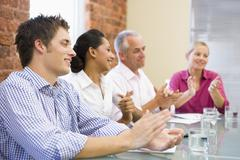Four businesspeople in boardroom applauding and smiling Stock Photos