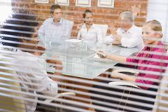 Five businesspeople in boardroom through window - stock photo