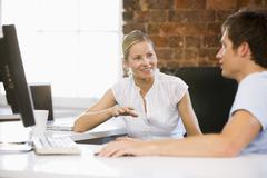 Stock Photo of Two businesspeople in office talking and smiling