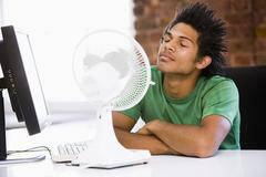 Businessman in office with computer and fan cooling off - stock photo