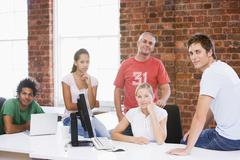 Five businesspeople in office space smiling - stock photo