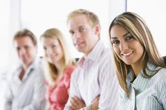 Four businesspeople sitting indoors smiling Stock Photos