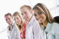 Four businesspeople sitting indoors smiling - stock photo