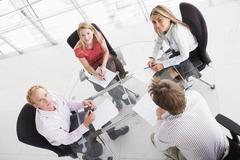 Four businesspeople in boardroom with paperwork smiling - stock photo