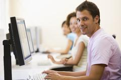 Three people sitting in computer room typing and smiling - stock photo