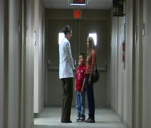 Doctor speaking with mom and son in hallway Stock Footage