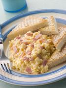 Cheesy keitetty muna kinkku ja paahdetut kolmiot Kuvituskuvat