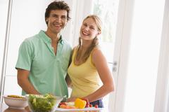 Couple in kitchen cutting up vegetables and smiling - stock photo