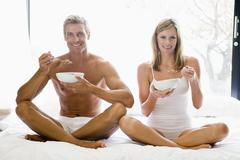 Couple sitting in bed eating cereal and smiling Stock Photos