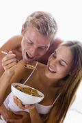Couple sitting in bedroom eating cereal and smiling Stock Photos