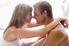 Couple in bedroom embracing and smiling - stock photo