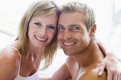 Stock Photo of Couple in bedroom embracing and smiling