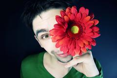 young guy with a flower on a black background - stock photo