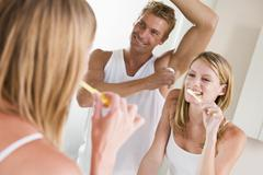 Couple in bathroom brushing teeth and applying deodorant Stock Photos