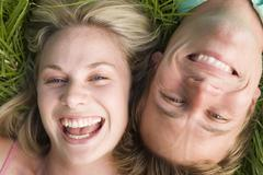 Couple lying in grass smiling Stock Photos