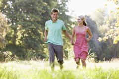 Couple running outdoors holding hands and smiling Stock Photos