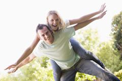 Man giving woman piggyback ride outdoors smiling Stock Photos