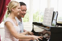 Couple playing piano and smiling Stock Photos
