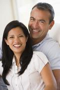 Couple in living room smiling - stock photo