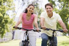 Couple on bikes outdoors smiling Stock Photos