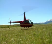 Robinson R-44 Helicopter takes off in gassy field Stock Footage