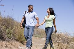 Couple walking on path holding hands and smiling - stock photo