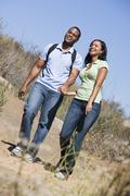 Couple walking on path holding hands and smiling Stock Photos