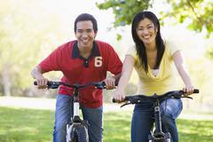 Couple on bikes outdoors smiling - stock photo