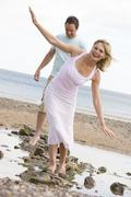 Couple at the beach walking on stones and smiling Stock Photos