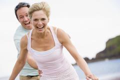 Couple at the beach smiling Stock Photos