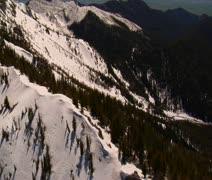 Aerial shot of snowy mountain saddle, pines around Stock Footage