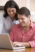Couple in kitchen with paperwork using laptop smiling Stock Photos