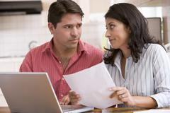 Couple in kitchen with paperwork using laptop looking unhappy - stock photo