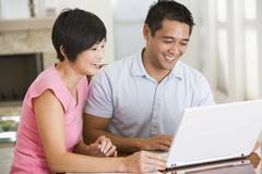 Couple in dining room with laptop smiling Stock Photos