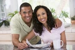 Couple in kitchen with newspaper and coffee smiling Stock Photos