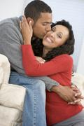 Couple in living room kissing and smiling - stock photo