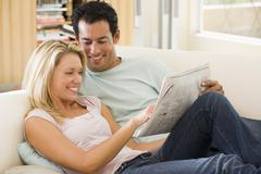 Couple in living room reading newspaper and smiling - stock photo