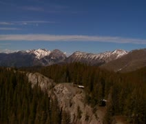 Aerial shot of pine forests, distant snowy mountains Stock Footage