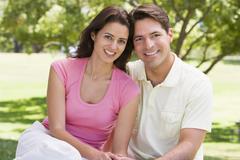 Couple sitting outdoors smiling - stock photo