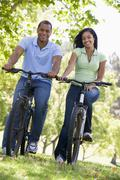 Couple on bikes outdoors smiling Stock Photos
