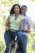 Couple on a bike outdoors smiling Stock Photos