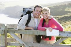 Couple on cliffside outdoors leaning on railing and smiling Stock Photos