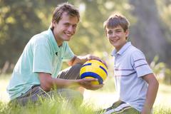 Man and young boy outdoors with soccer ball smiling Stock Photos