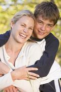 Woman and young boy embracing outdoors and smiling Stock Photos
