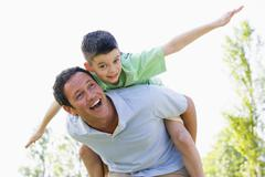 Man giving young boy piggyback ride outdoors smiling Stock Photos
