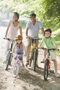 Family sitting on bikes on path smiling - stock photo