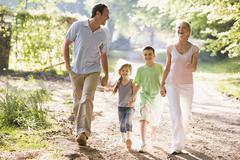Family running outdoors holding hands and smiling Stock Photos